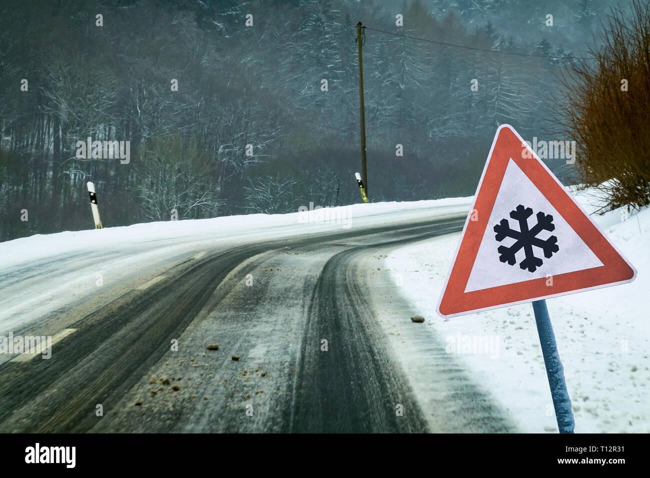 Snowy curvy road with traffic sign Snowy curvy road with traffic sign - Stock Image