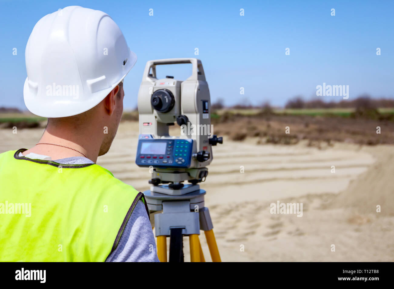 Surveyor engineer is measuring level on construction site. Surveyors ensure precise measurements before undertaking large construction projects. Stock Photo