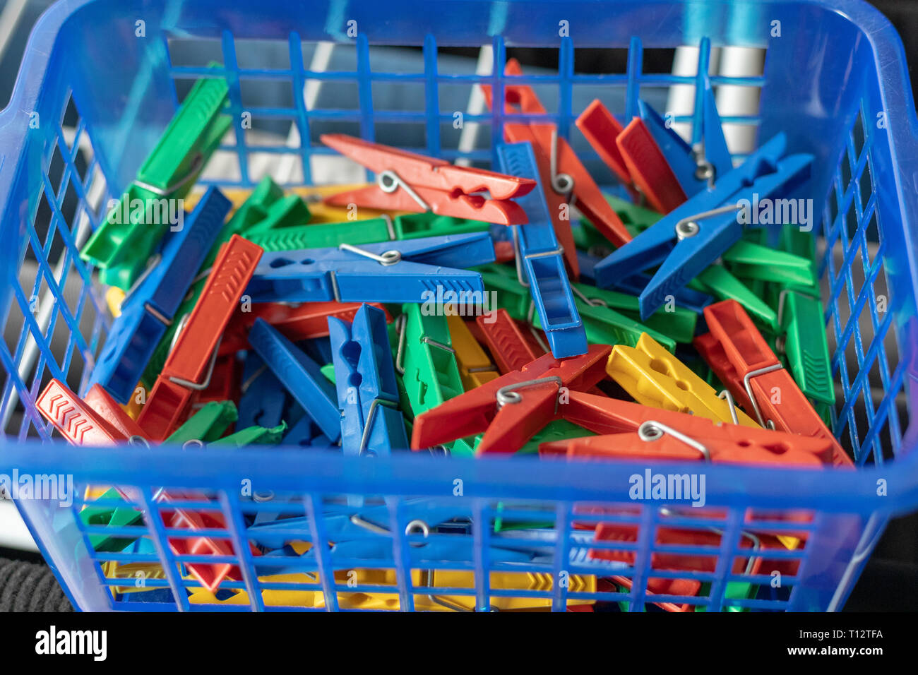 Colorful clothespins in a blue basket - Stock Image