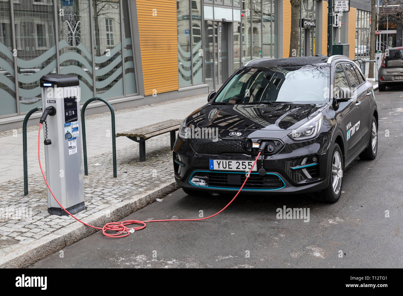 A Kia Niro Plug In Hybrid car attached to an electrical charging station by the side of a road in the town of Trondheim in Norway. Stock Photo