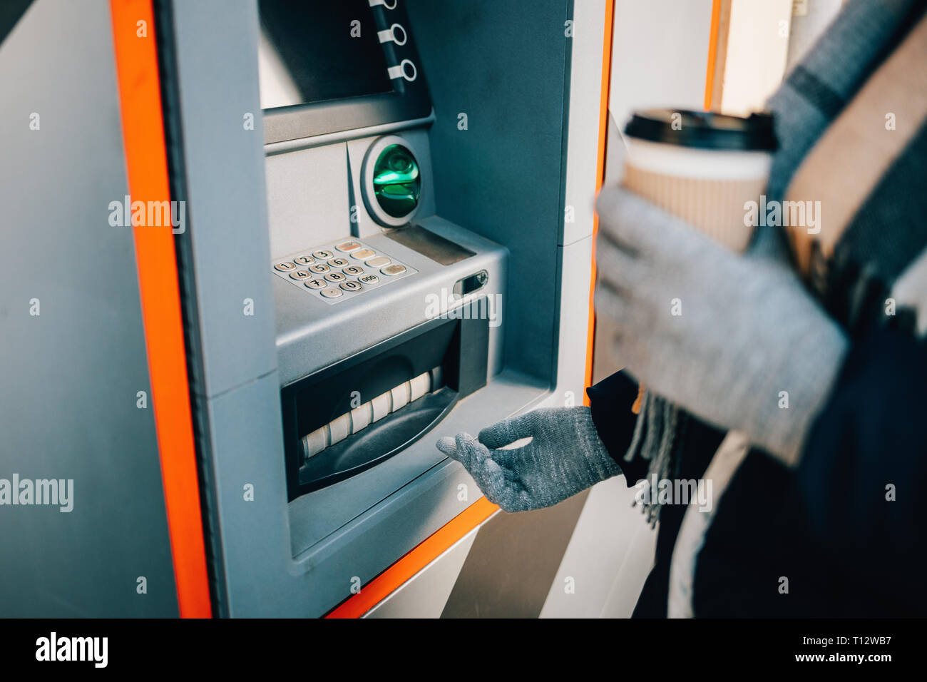 Unrecognizable young woman withdrawing cash using ATM and drinking coffee on city street in winter day, close-up. - Stock Image