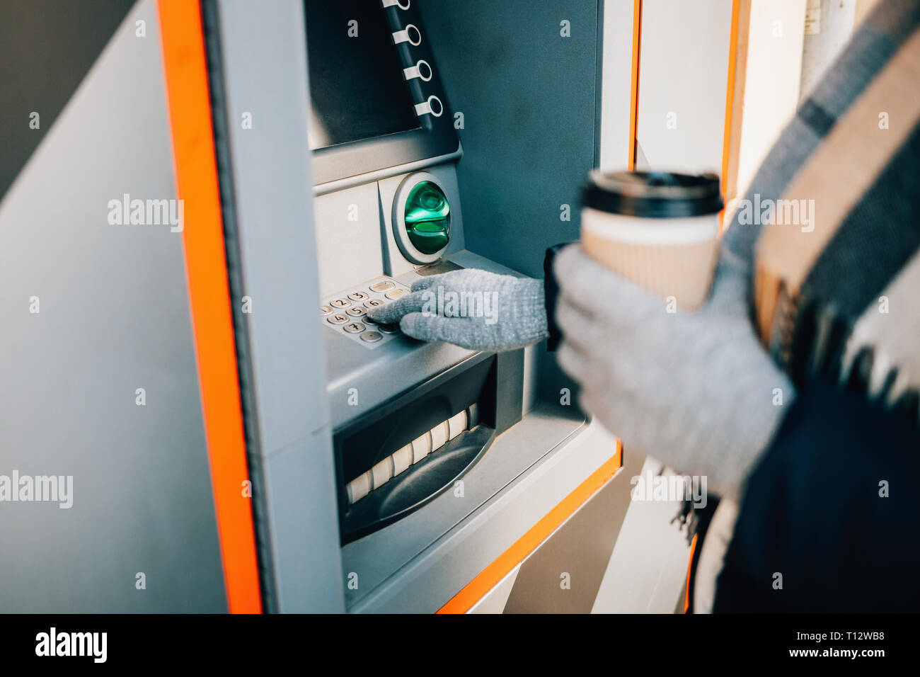 Close-up young woman pressing buttons on ATM keypad entering PIN and drinking coffee on city street in winter day. - Stock Image