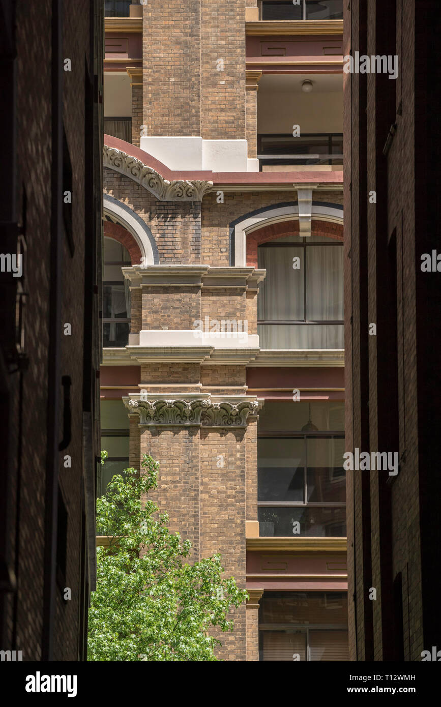 Looking through a darkened narrow ally to a sunlit complex and ornate multistory (multistorey) brick building in Sydney Australia's CBD - Stock Image