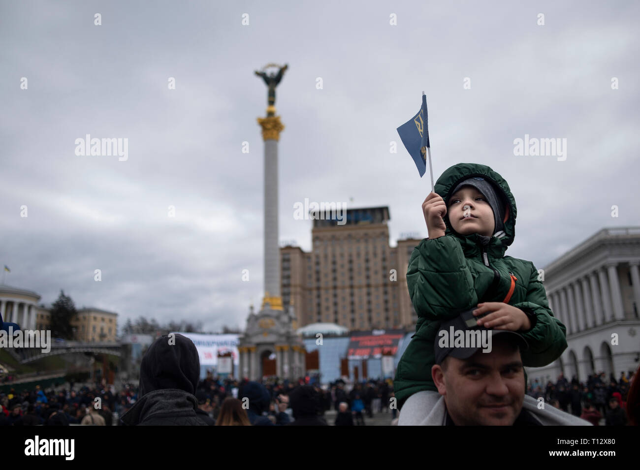 A boy seen waving a flag as he watches on during the demonstration.  Protesters gathered in Maidan Square then marched to the Presidential Administration building to call on President Petro Poroshenko to bring corrupt governmental officials to justice. With the Ukrainian Elections being held at the end of March the political tensions run very high. Stock Photo