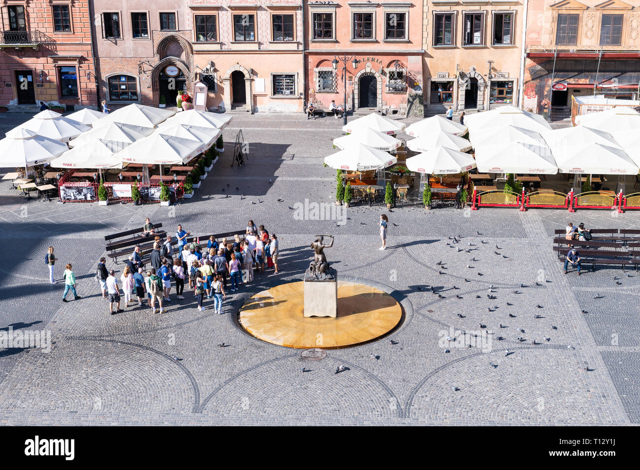 Warsaw, Poland - August 22, 2018: Historic old town market square with high angle view of buildings and tour group by fountain in morning Stock Photo