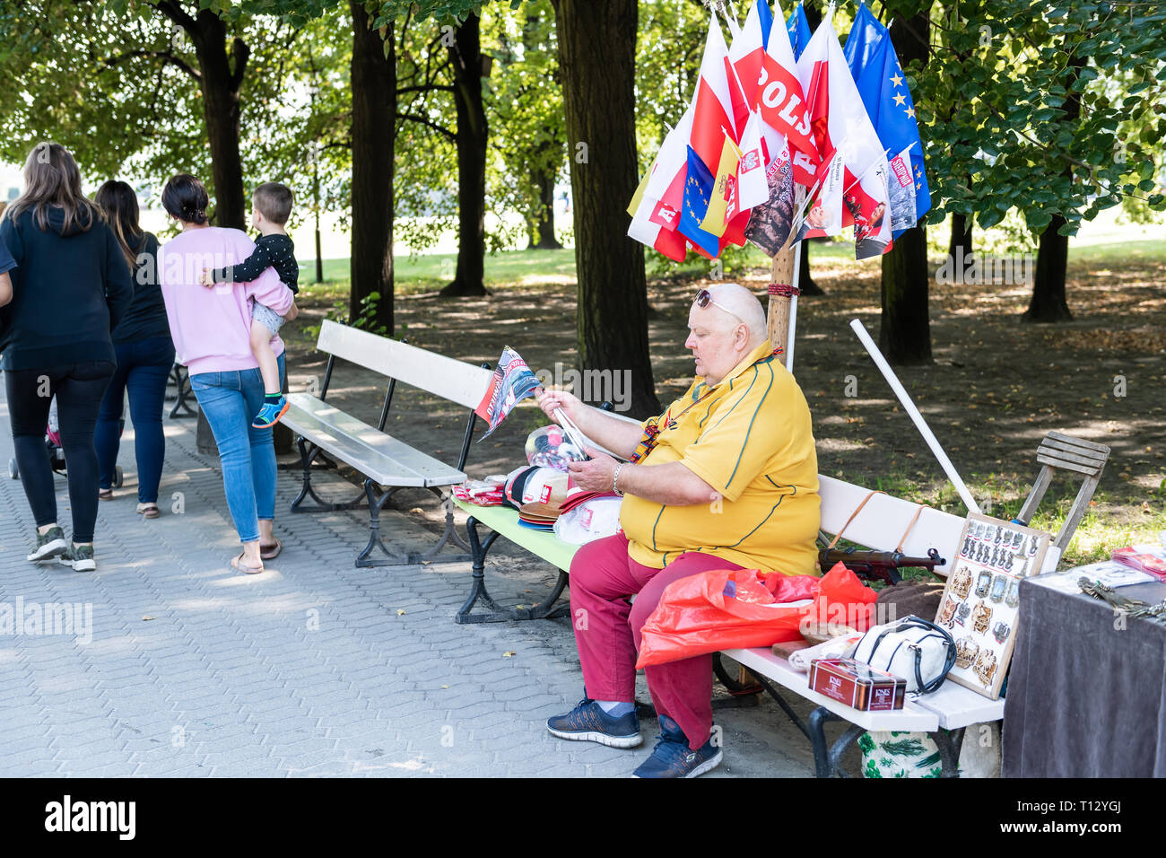 Warsaw, Poland - August 23, 2018: People woman vendor selling souvenirs Polish European Union flags on bench in summer Saxon Gardens Park - Stock Image