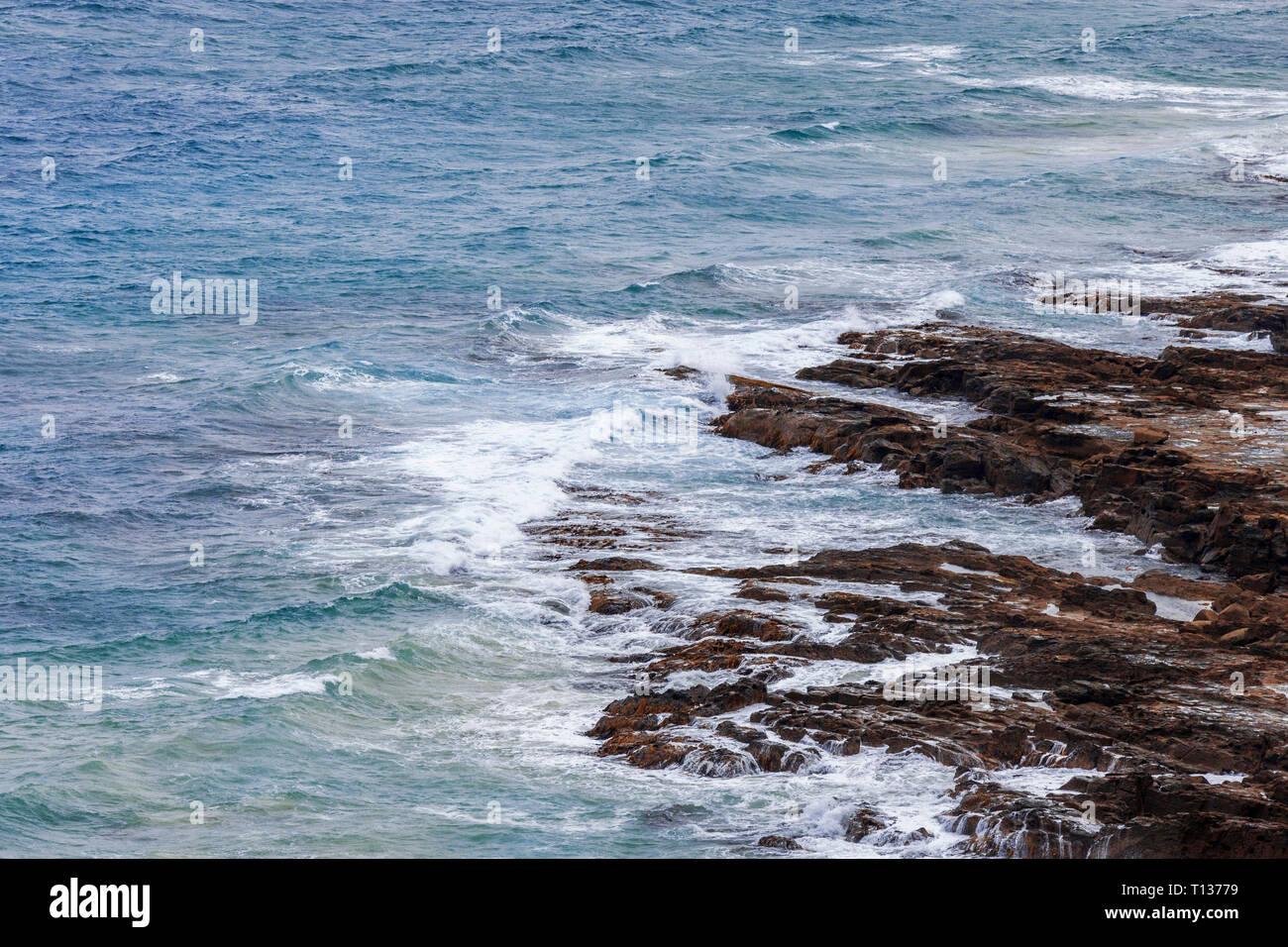 Rough waves crashing onto rocks below. - Stock Image
