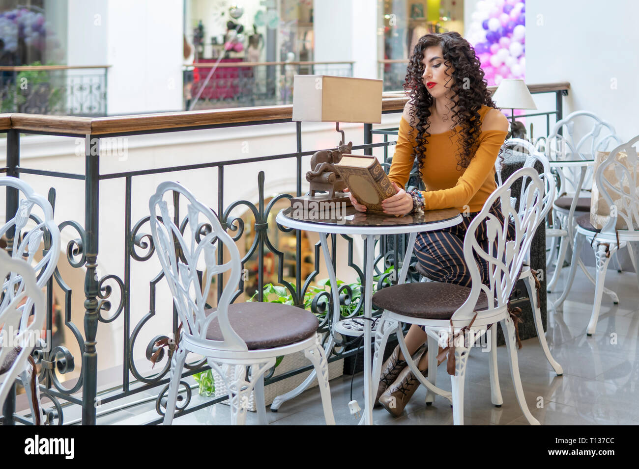 beautiful curly-headed woman with a closed book at a table in a cafe - Stock Image