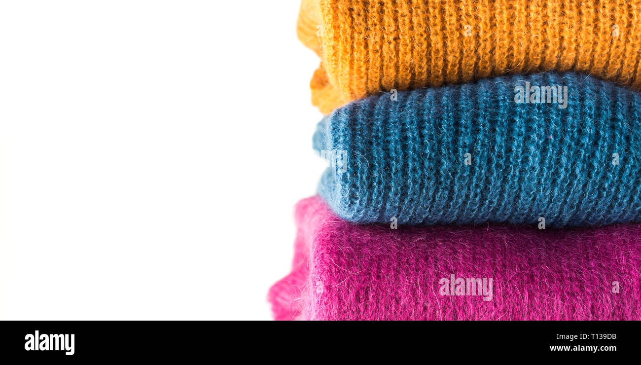 Pile of cozy winter woolen sweaters isolated on white