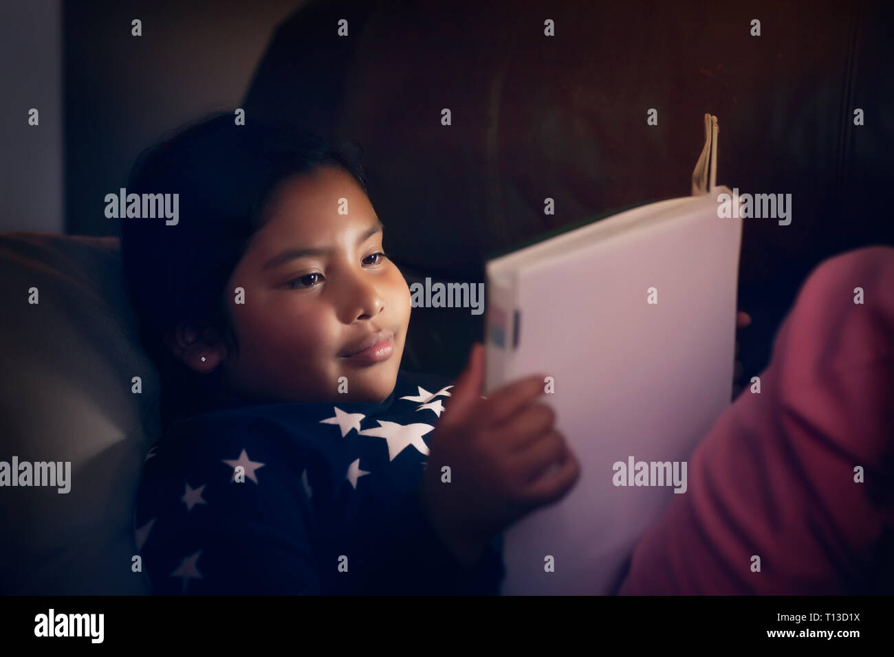 Indian little girl wearing pajamas with stars while reading a story book at night and smiling. - Stock Image