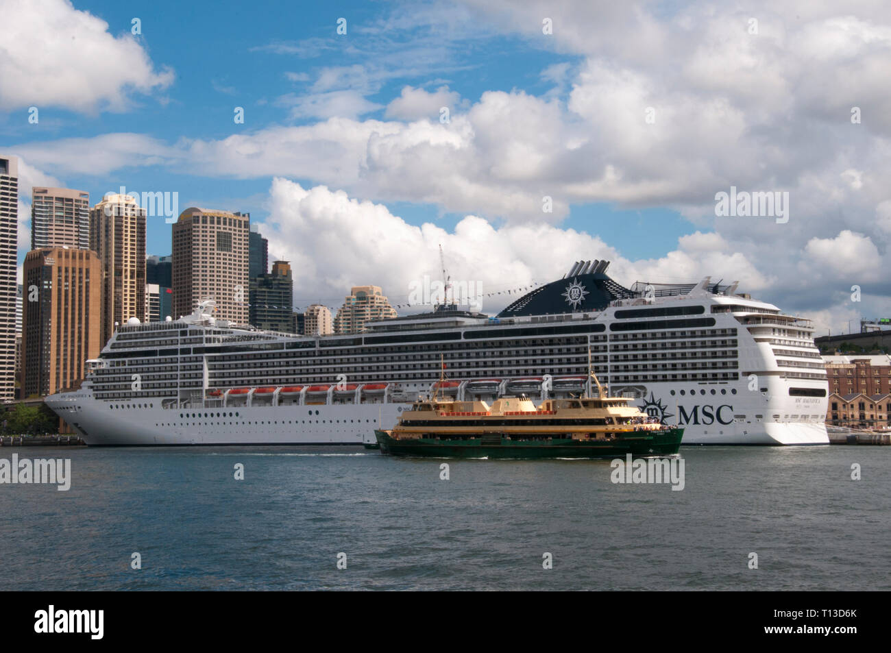 A Sydney Harbour commuter ferry steaming past the 'MSC Magnifica' cruise liner moored at Circular Quay, Sydney, Australia Stock Photo