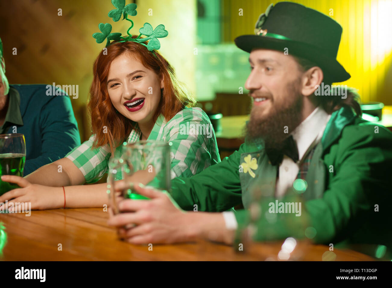 Red-haired pretty girl with shamrock headwear laughing loudly - Stock Image
