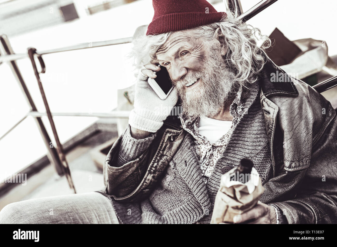 Unhygienic man with bottle in hand calling with smartphone. - Stock Image