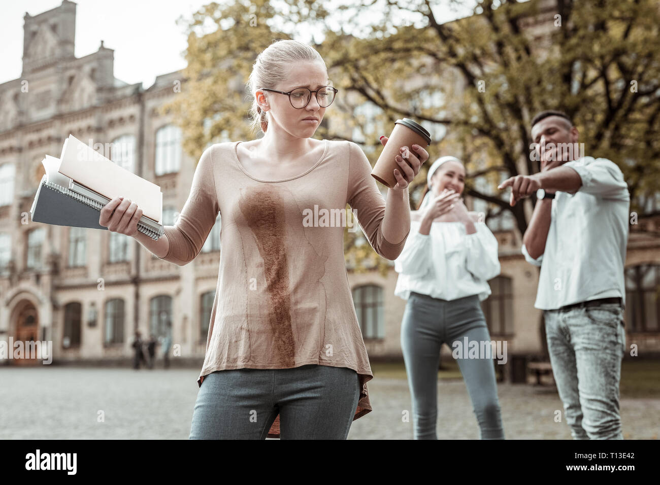 Negative delighted girl standing on the foreground - Stock Image