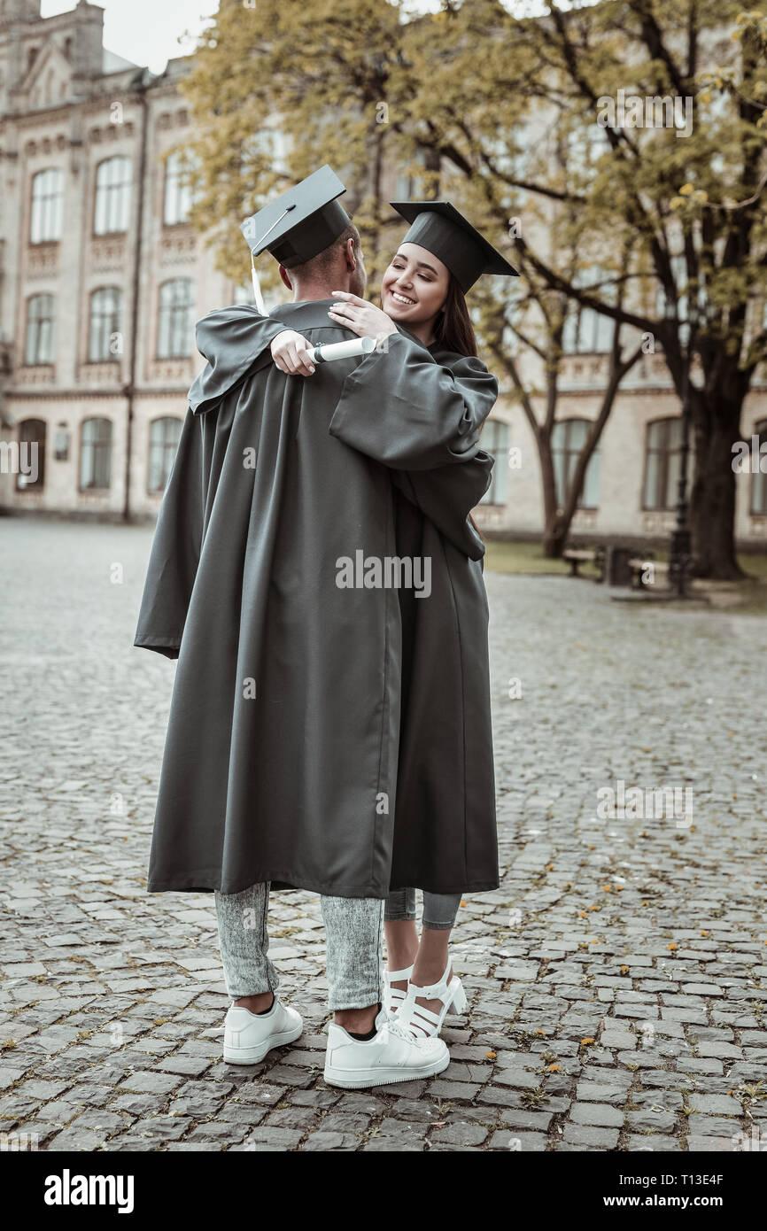 Cheerful international students wearing uniform for graduation - Stock Image