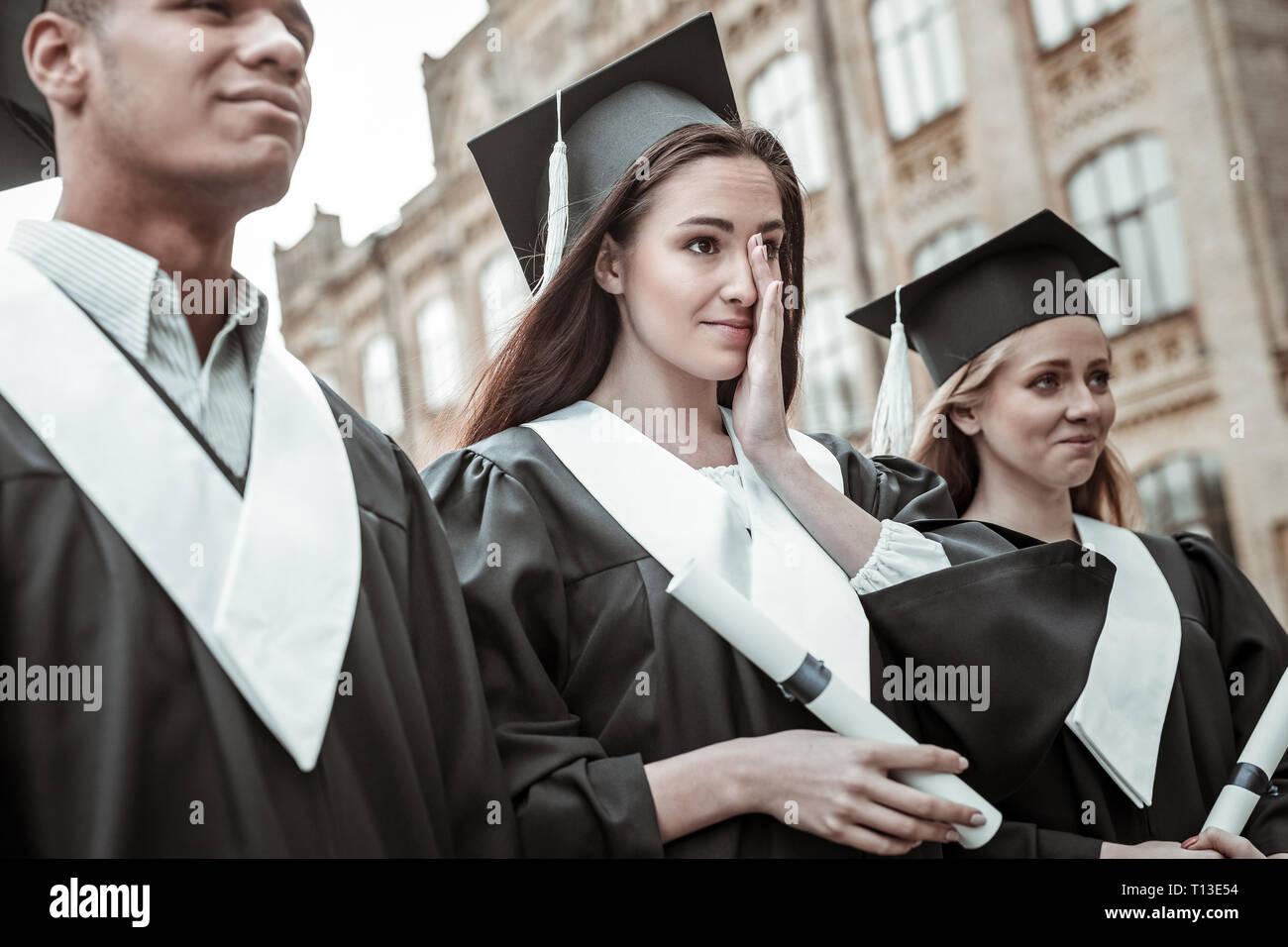 Tender brunette longhaired girl wiping her tears - Stock Image