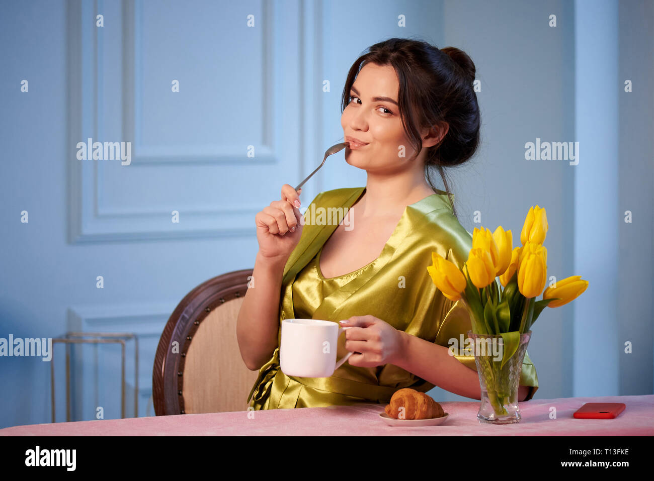 Beautiful young woman in sleepwear drinking morning coffee with croissants. - Stock Image