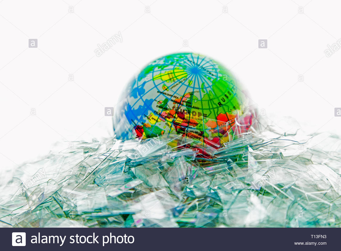 A studio creation of the Earth floating in a sea of clear plastic shards. Concept: plastic pollution, environmental damage, drowning the Earth - Stock Image