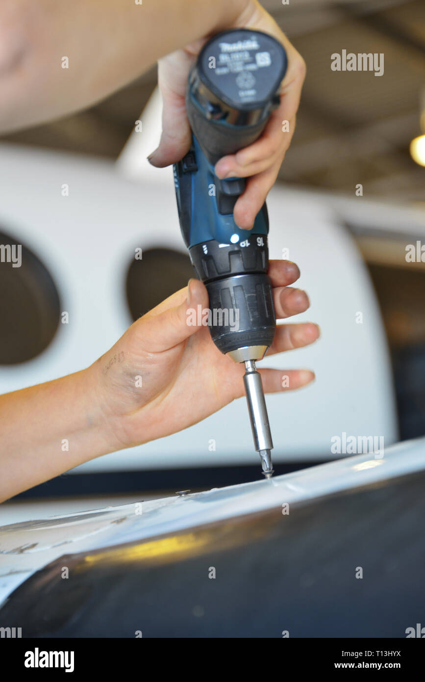 A portrait view, close up of an aeronautical engineers hands with a power drill. An aircrafts windows are visible in the background. - Stock Image