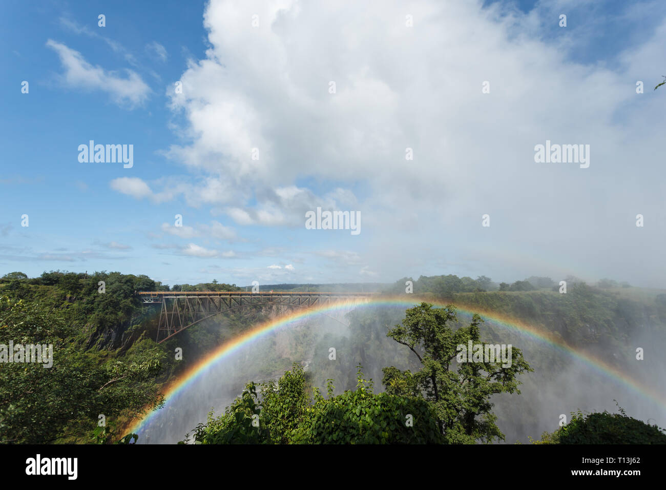 Rainbow shaped like Livingston bridge arches over gorge in Africa - Stock Image