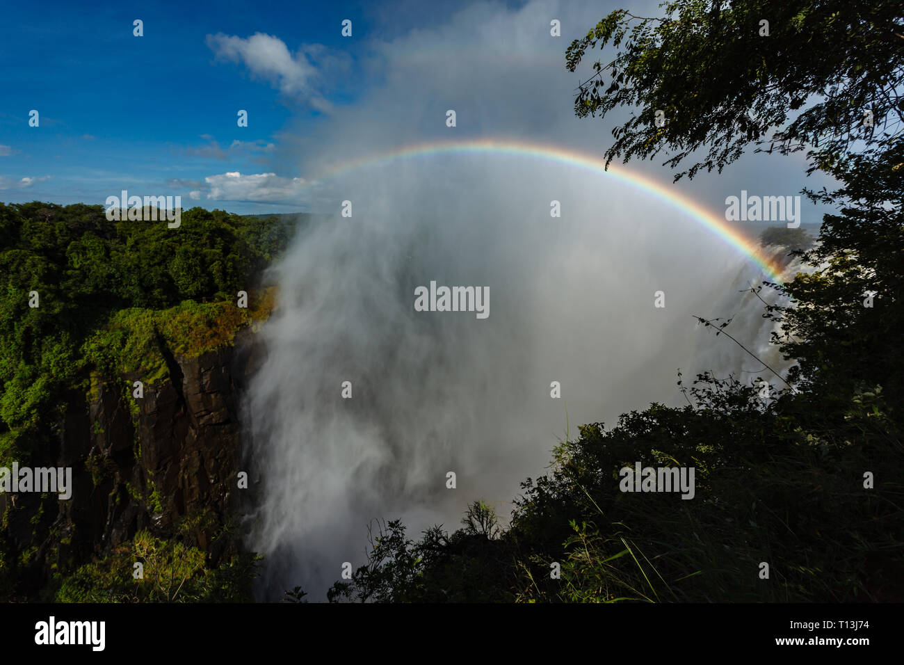 Brilliantly colored rainbow rises high in the mist over Victoria Falls Africa - Stock Image