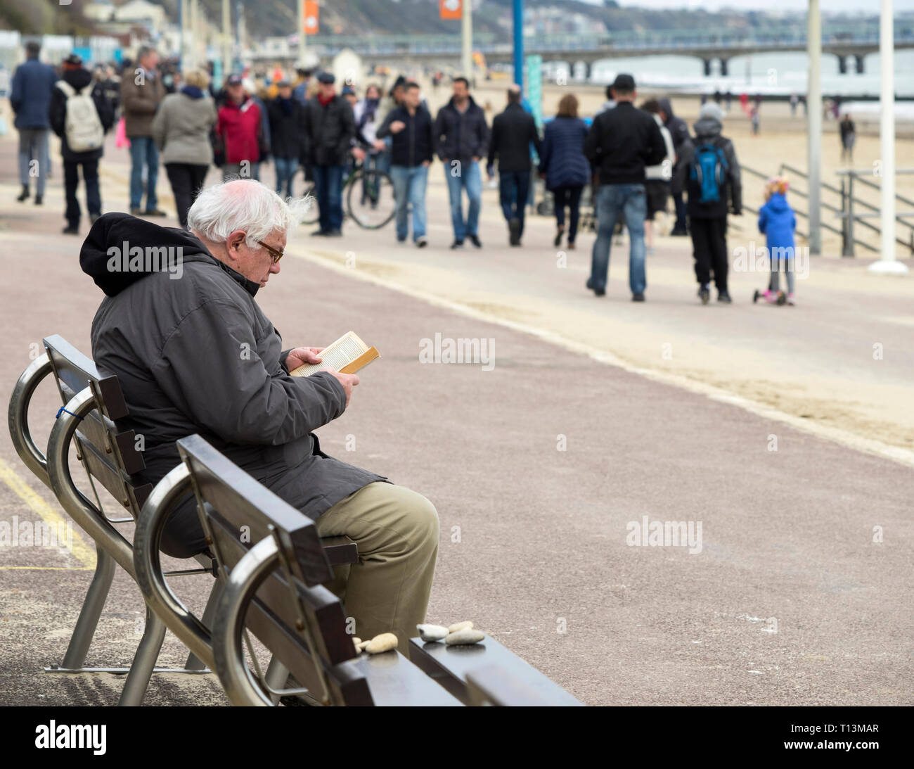 White-haired man sitting on a bench on the promenade at Bournemouth reading a book with people walking nearby. - Stock Image