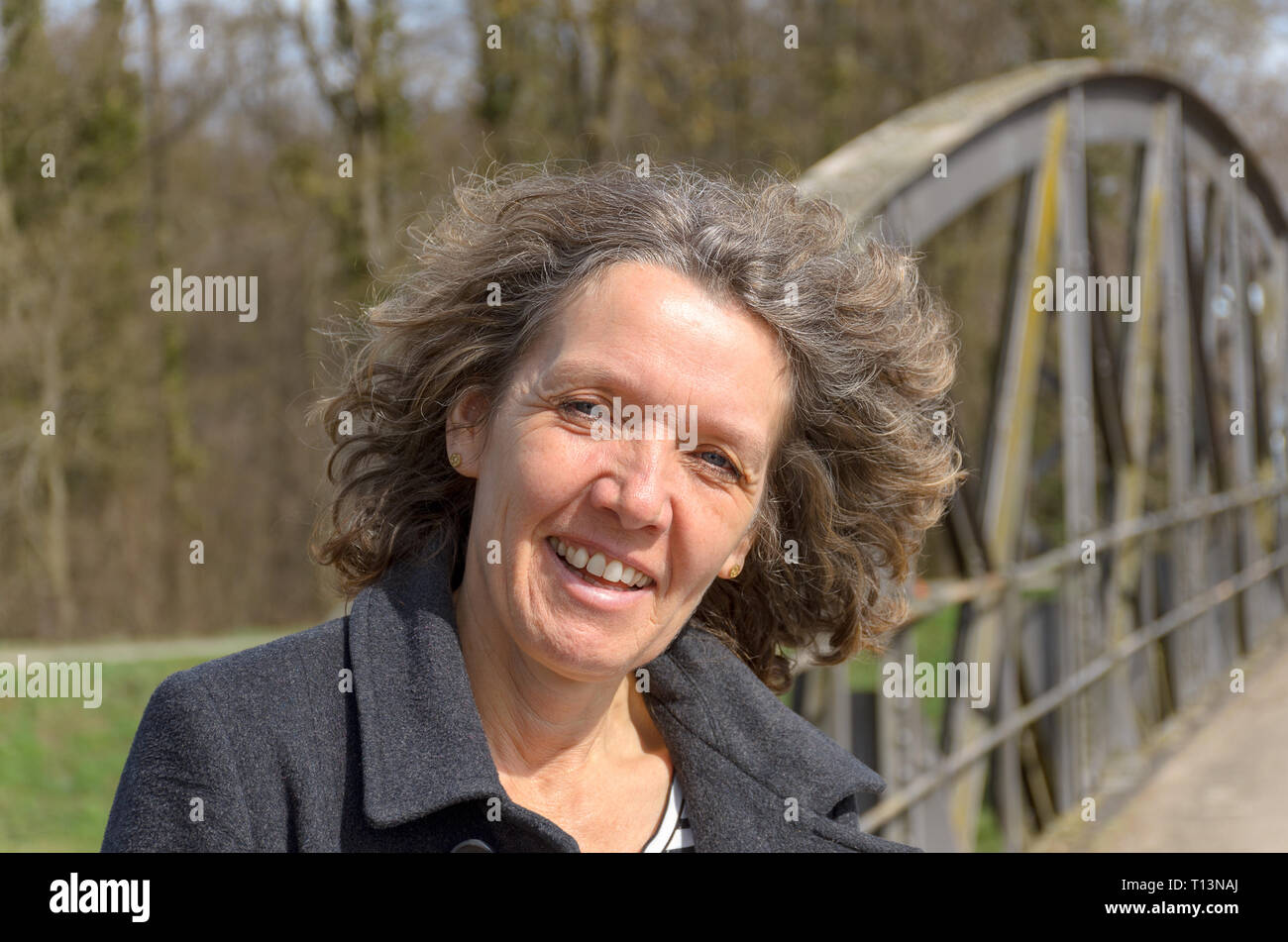 Smiling friendly woman with tousled hair standing on a bridge in the countryside in spring sunshine looking at camera with a happy smile - Stock Image