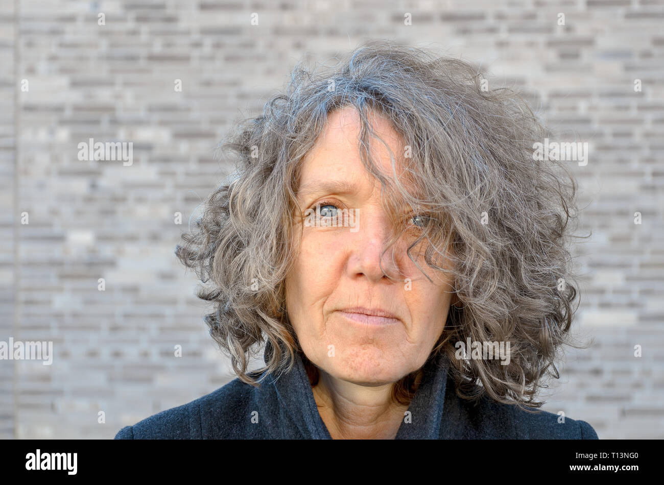 Portrait of an attractive middle-aged woman with tousled curly hair posing in front of a grey brick wall looking into the camera - Stock Image