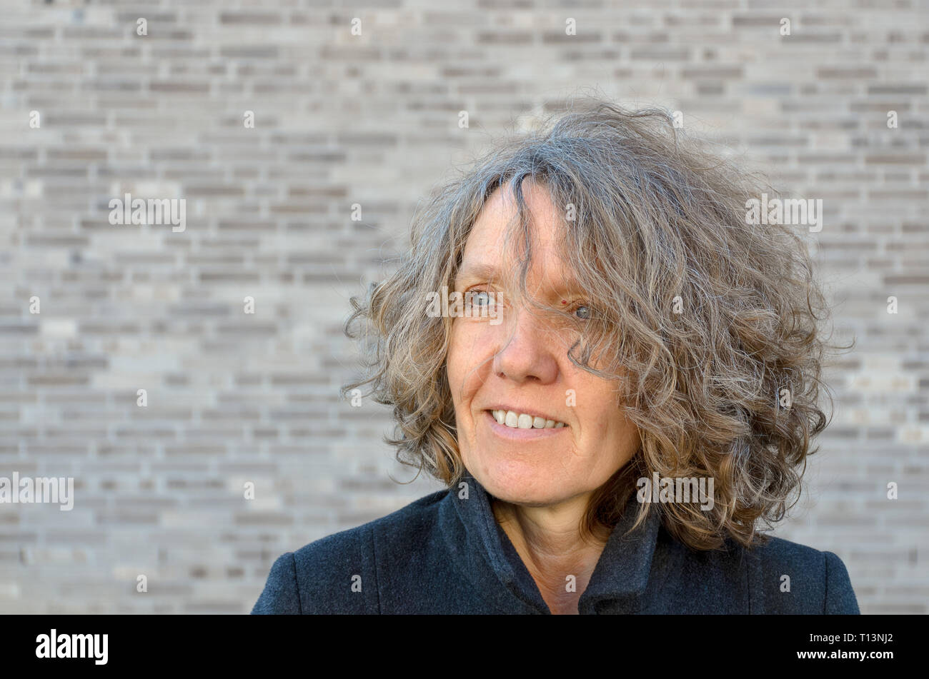 Mature smiling woman with curly tousled hair looking off to the side as she poses in front of a grey brick wall with copy space - Stock Image