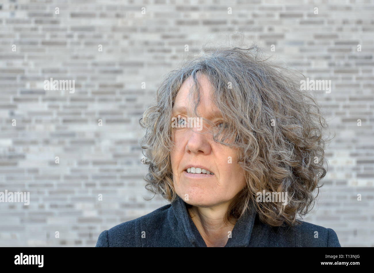 Mature serios woman with curly tousled hair looking off to the side as she poses in front of a grey brick wall with copy space - Stock Image