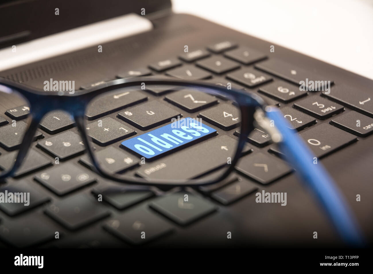 View of the PC keyboard through the lens of the glasses on the button with the written Oldness Stock Photo