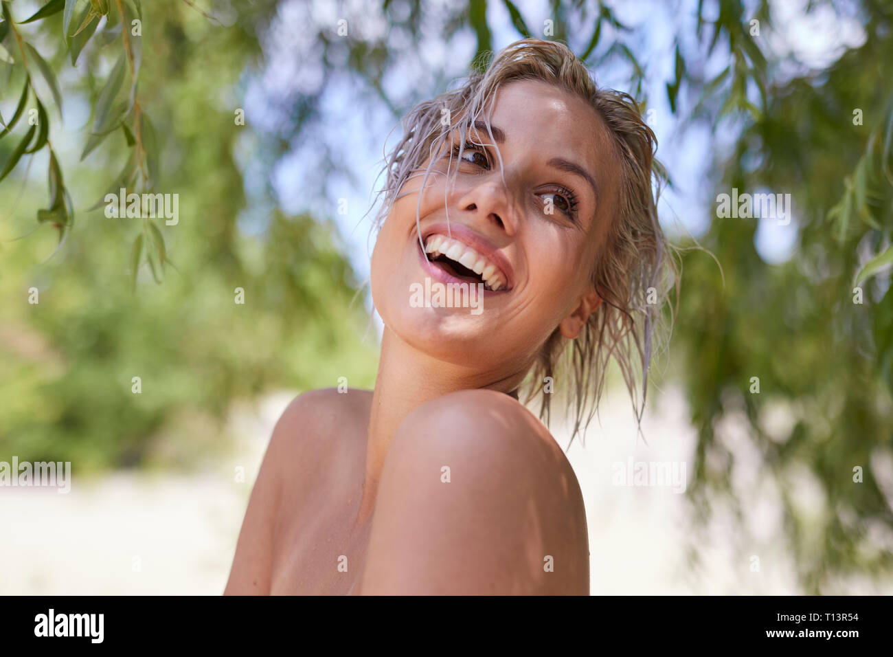 Portrait of a beautiful woman with wet hair and bare shoulders, laughing - Stock Image