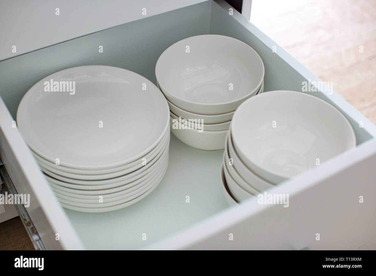 Opened drawer with white plates and bowls - Stock Image