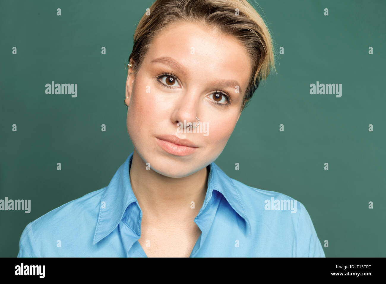 Portrait of young woman with nose piercing in front of green background - Stock Image
