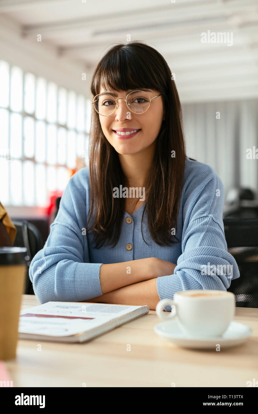 Portrait of smiling young woman with notepad at desk in office - Stock Image