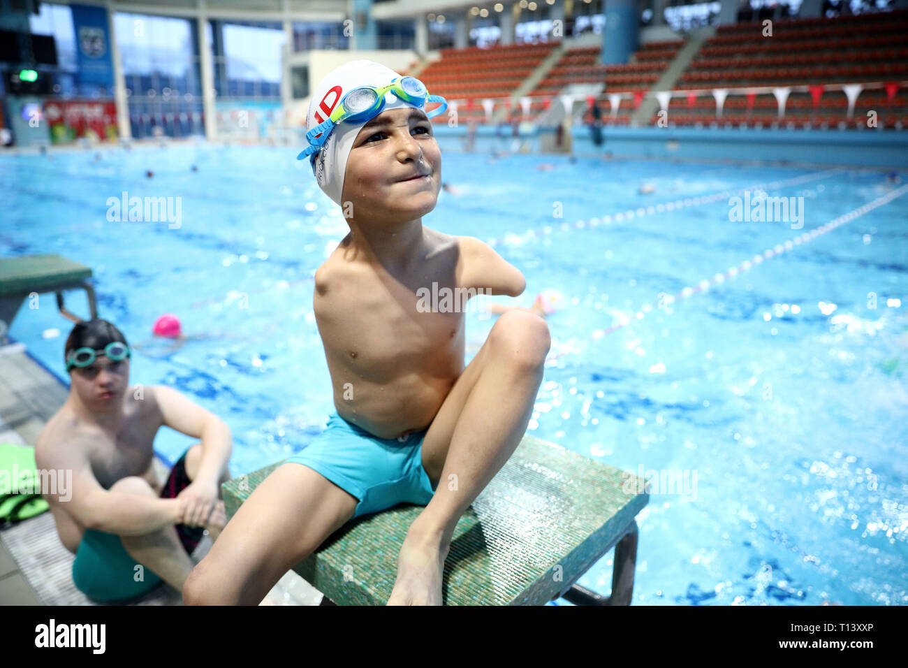 Sarajevo. 21st Mar, 2019. Photo taken on March 21, 2019 shows Ismail Zulfic (R) at the Olympic Pool Otoka in Sarajevo, Bosnia and Herzegovina (BiH). Eight-year-old Ismail Zulfic from Bosnia and Herzegovina was born without both arms, and with one deformed leg - yet his successes in the swimming pool have made him an inspiration for many. Credit: Nedim Grabovica/Xinhua/Alamy Live News - Stock Image