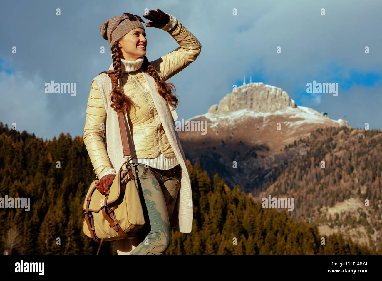 smiling young traveller woman in hiking clothes with bag in Alto Adige, Italy looking into the distance. - Stock Image
