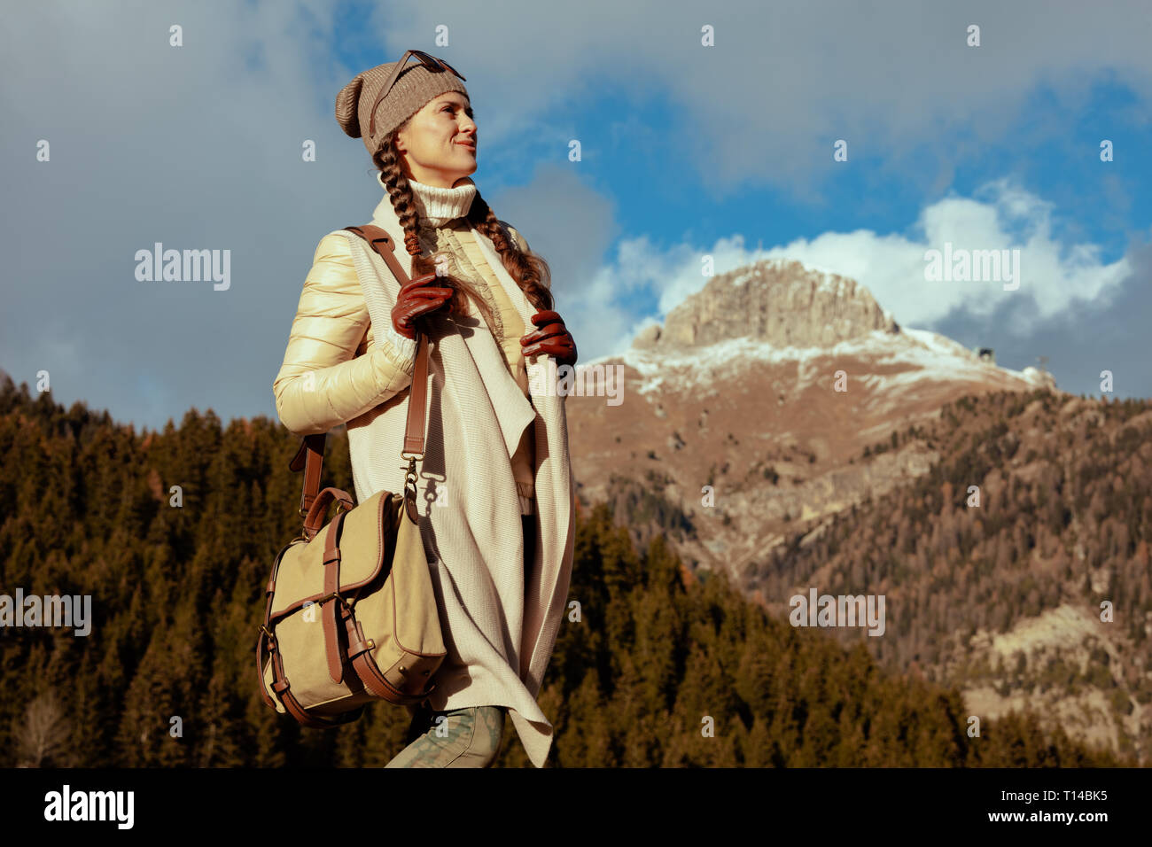 adventure woman hiker in hiking clothes with bag looking into the distance against mountain scenery in Alto Adige, Italy. - Stock Image