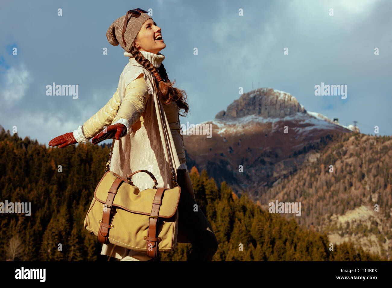 happy active traveller woman in hiking clothes with bag rejoicing against mountain scenery in South Tyrol, Italy. - Stock Image