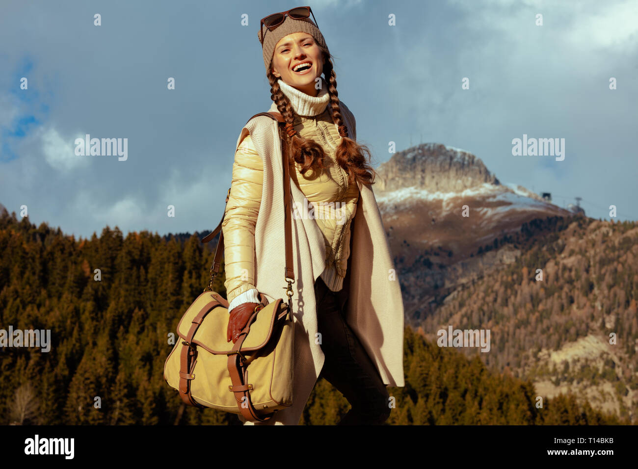 Portrait of happy active traveller woman in hiking clothes with bag against mountain landscape in South Tyrol, Italy. - Stock Image