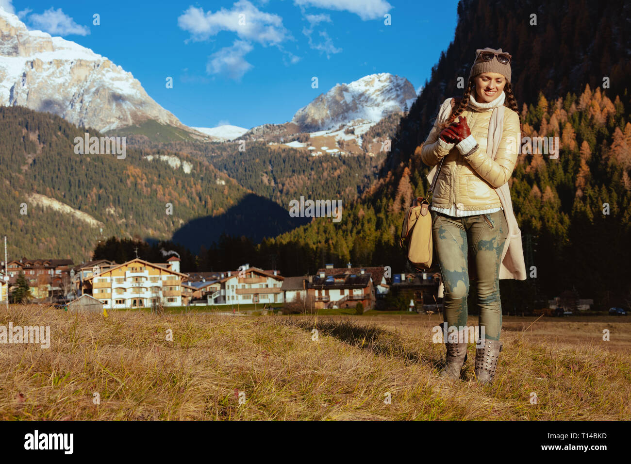 happy adventure woman hiker in hiking gear with bag enjoying promenade against mountain scenery in South Tyrol, Italy. - Stock Image