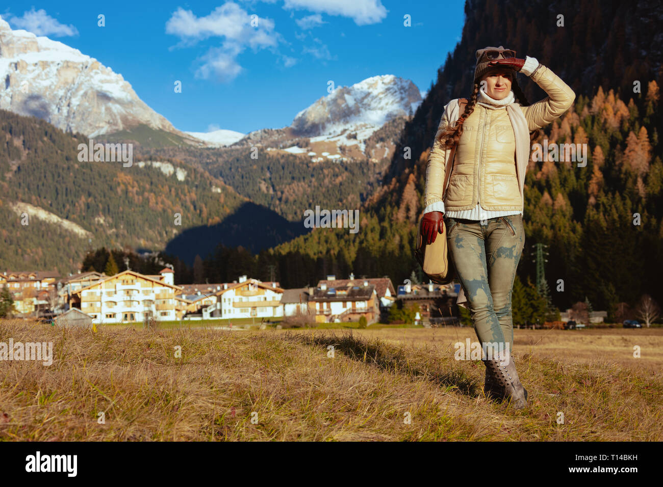 fit woman hiker in hiking gear with bag in Alto Adige, Italy looking into the distance. - Stock Image