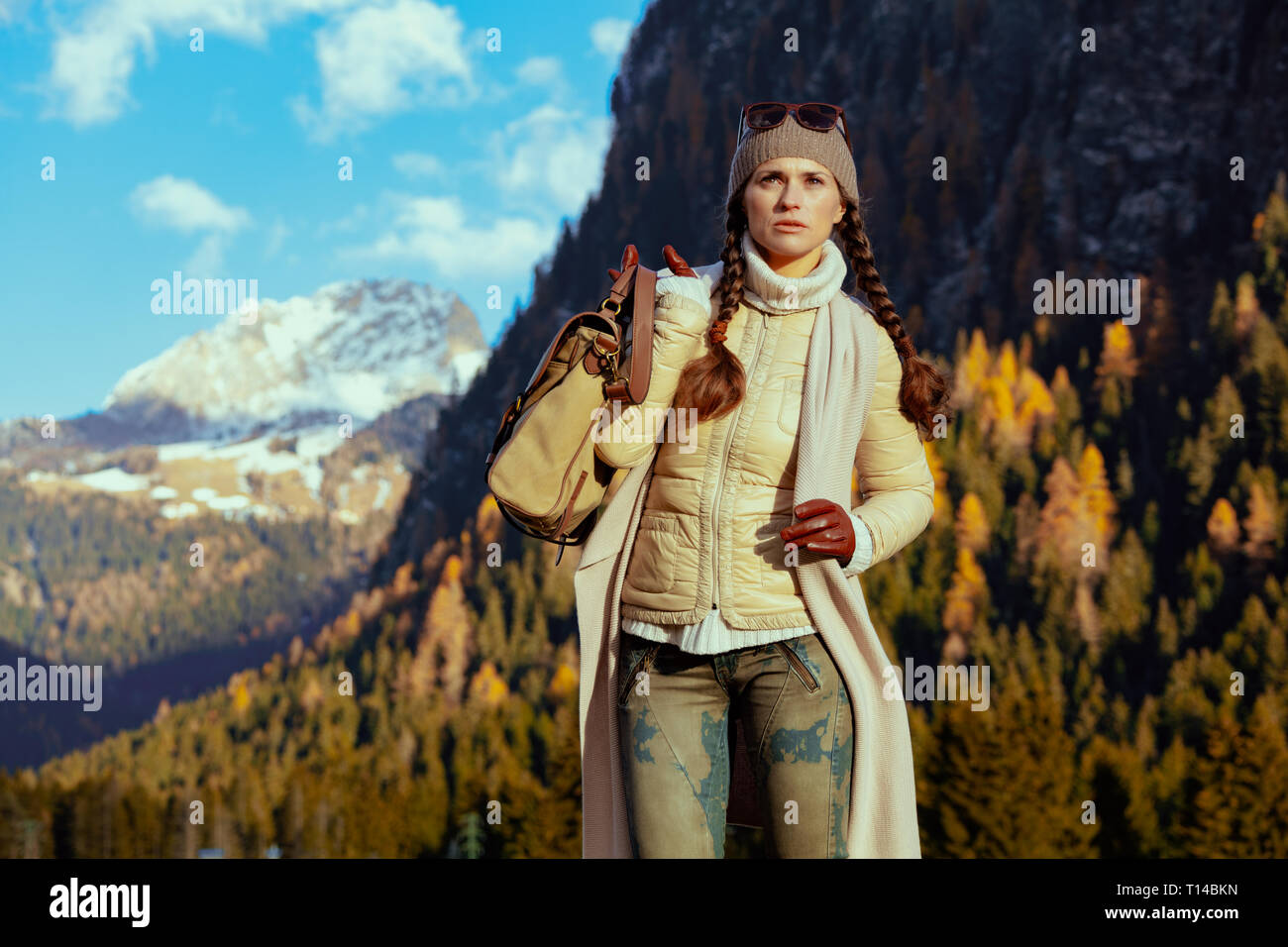 healthy tourist woman in hiking clothes with bag looking into the distance against mountain scenery in Alto Adige, Italy. - Stock Image
