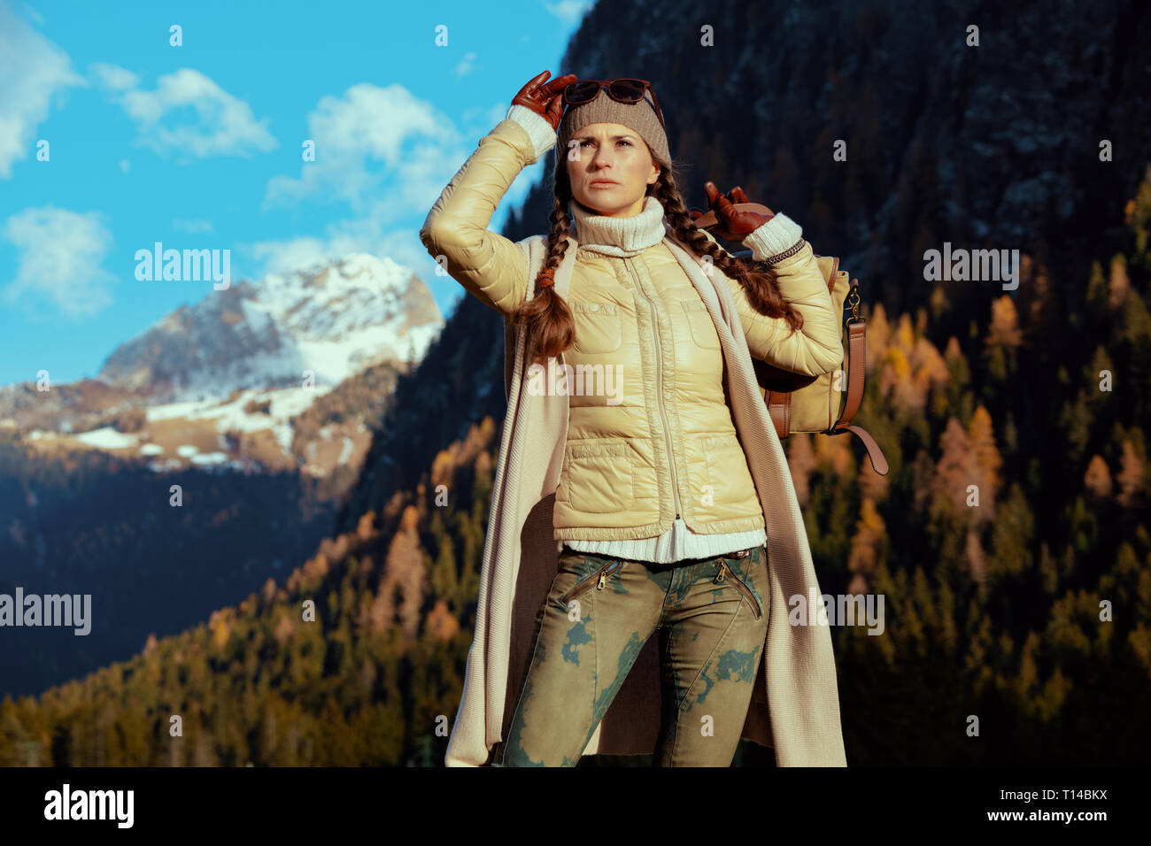 fit woman hiker in hiking gear with bag in the front of mountain landscape in Alto Adige, Italy looking into the distance. - Stock Image