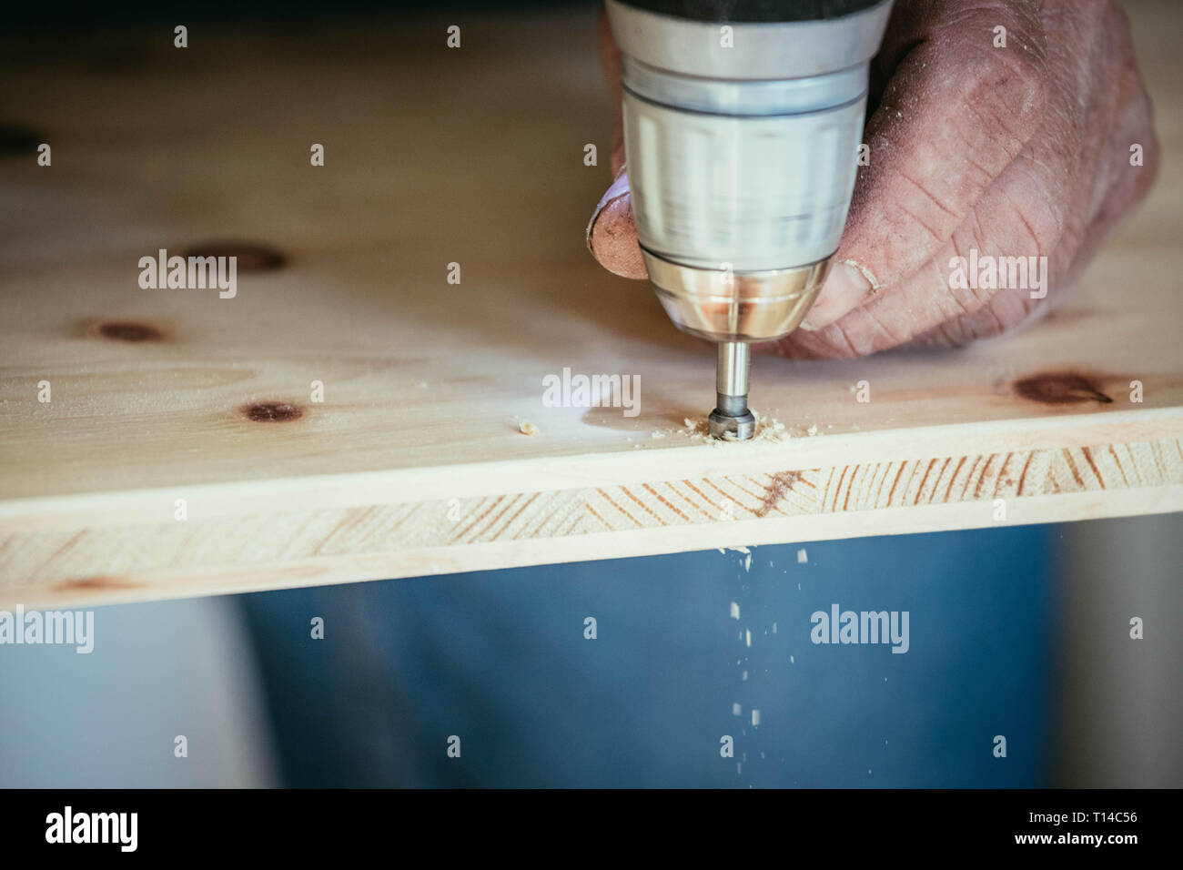 Craftsman is drilling in wood with drilling machine Stock Photo