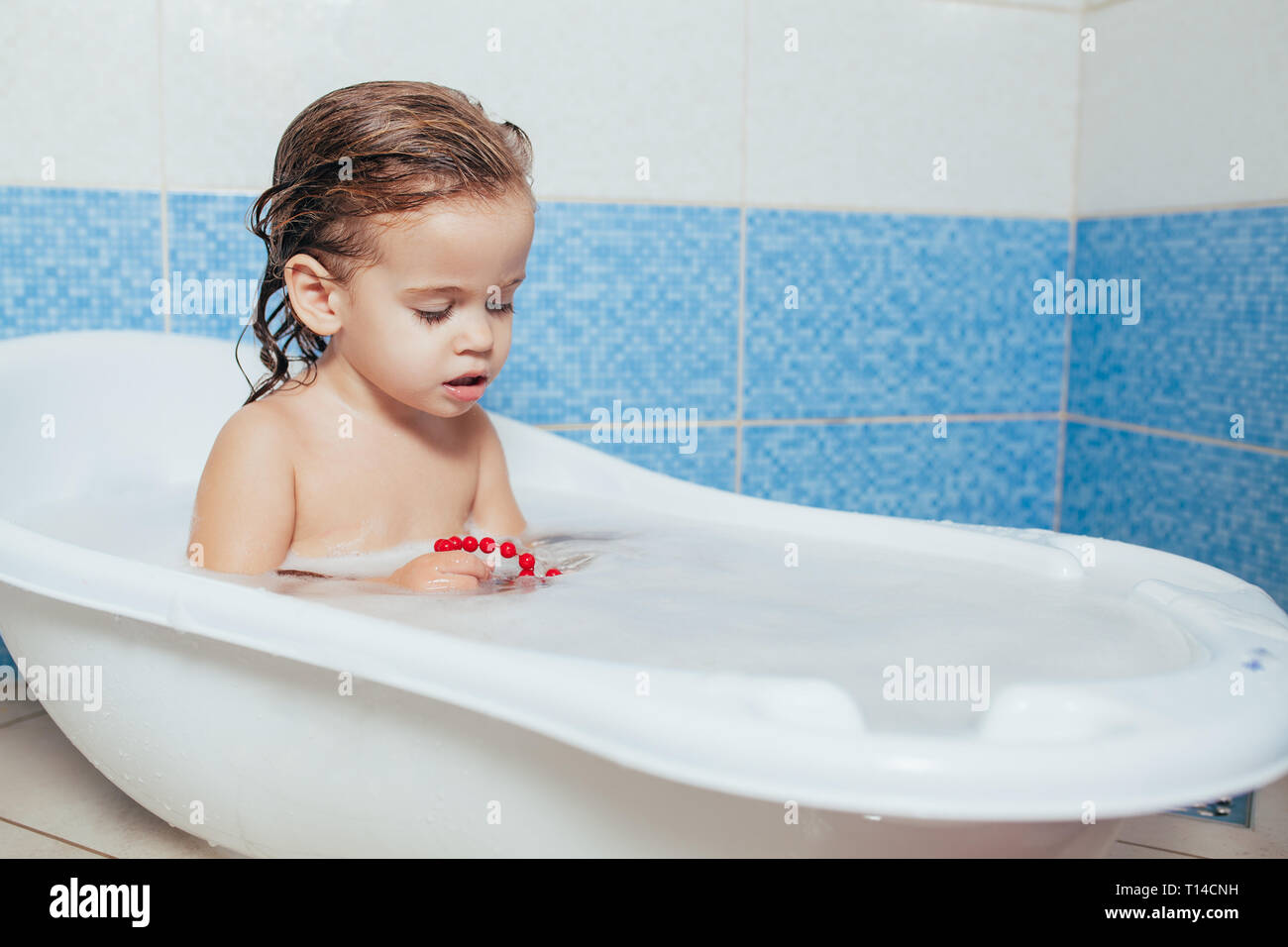 c0e8b22e321b7 Fun cheerful happy toddler baby taking a bath playing with foam bubbles. Little  child in