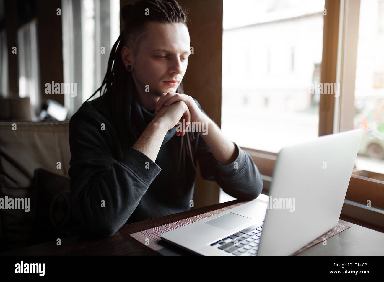Young Businessman with dreadlock having doing his work in cafe with laptop. - Stock Image