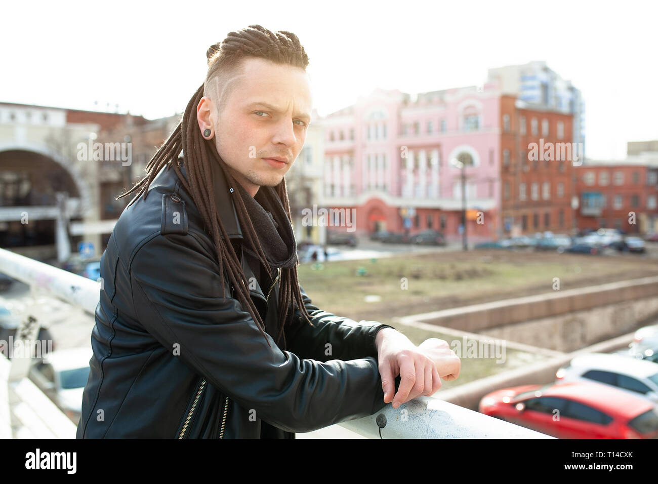 rocker rock star young man walking on the city street autumn day - Stock Image
