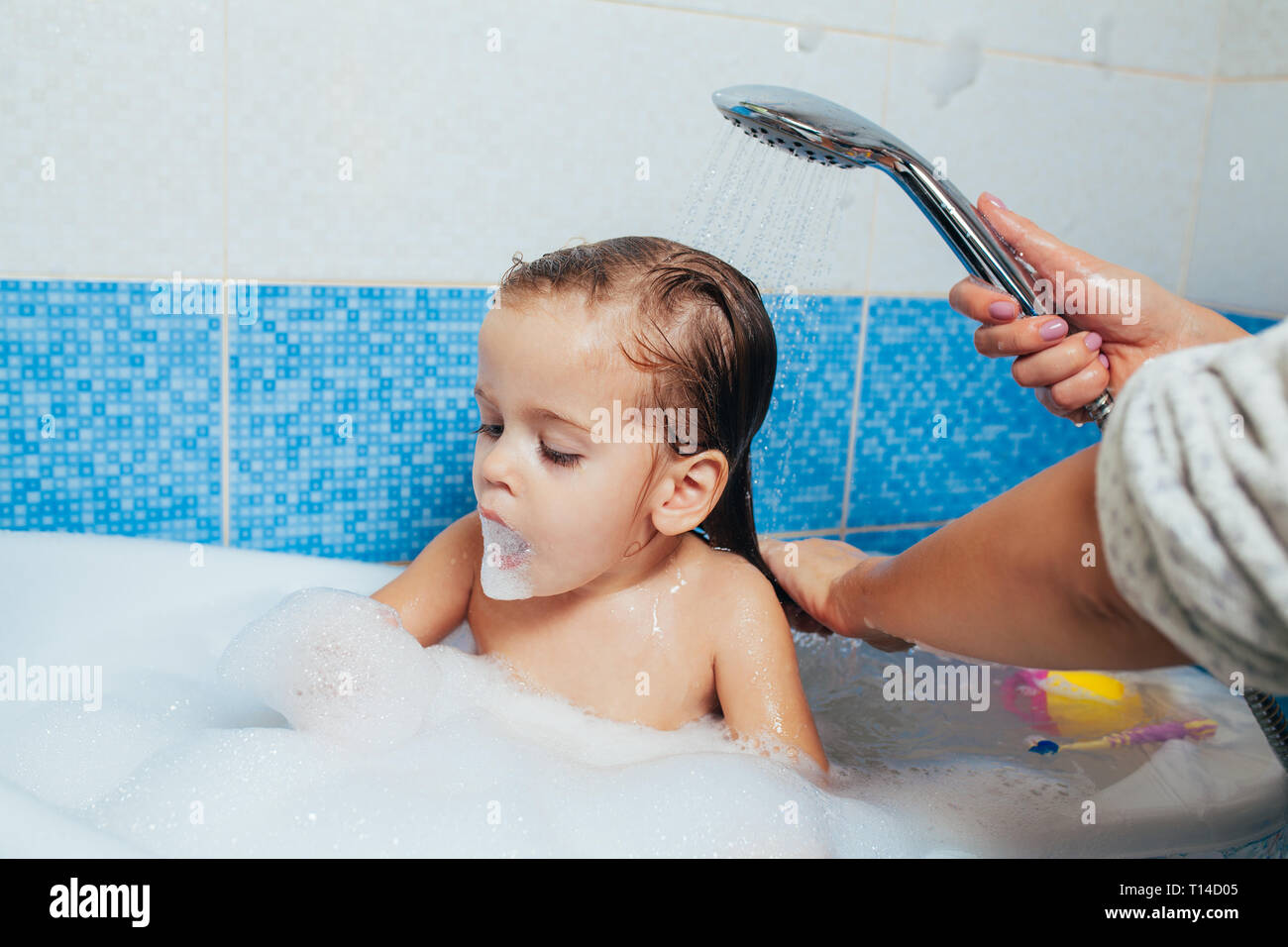 2ff5fa88c8893 Beautiful little girl taking a bath at home. A cute baby is sitting in the