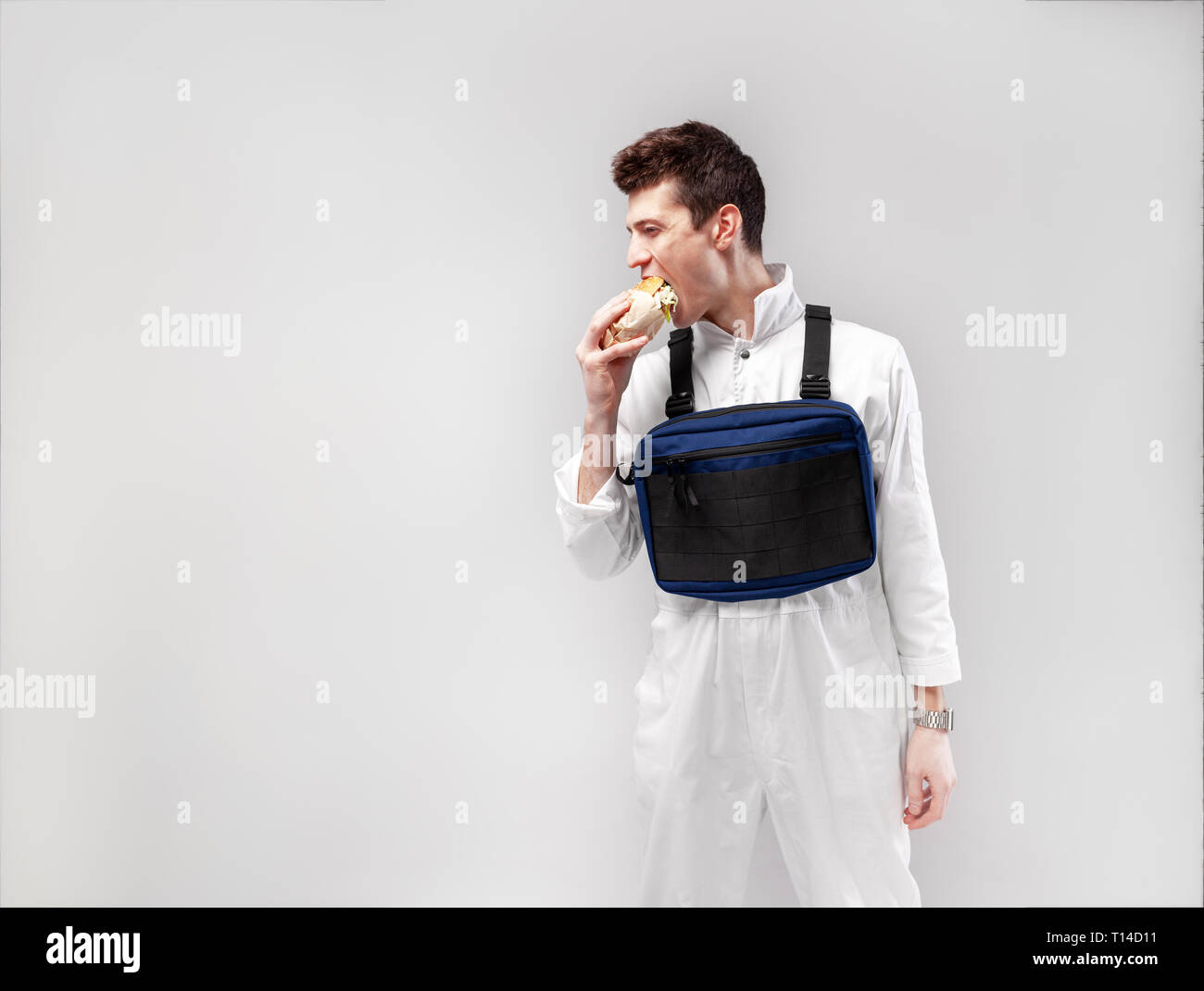 Young stylish male worker with chest rig bag is eating a tasty juicy burger on a white background - Stock Image